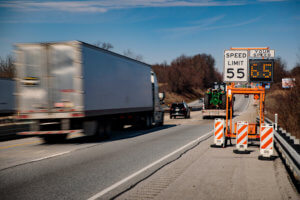 Truck speeding past 55 mph speed limit sign with a digital sign reading 65 mph.